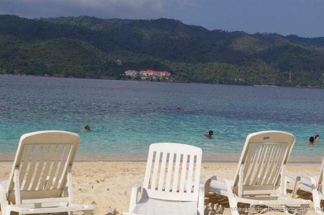 White beach chairs beach waters and a resort in the disatance from Cayo Levantado.jpg