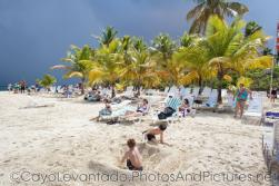 Kids play in the sand as storm clouds hover over Cayo Levantado.jpg