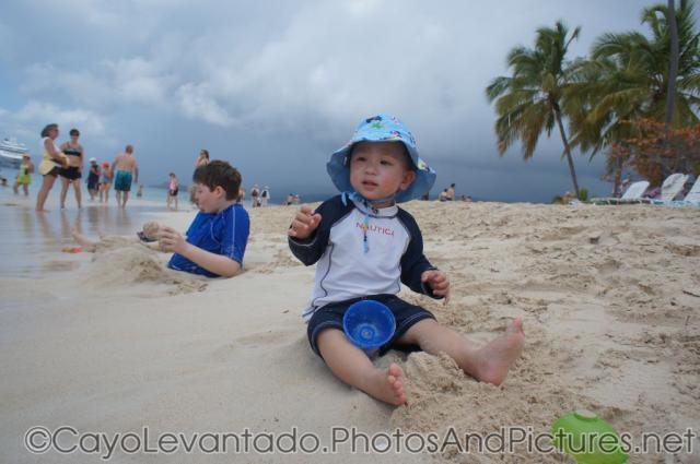 Darwin sits on the beach sand of Cayo Levantado.jpg